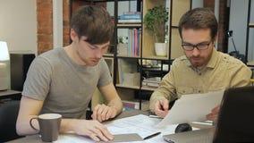 Les hommes de collègues explique des plans de travail se reposant derrière l'ordinateur portable à l'intérieur du bureau clips vidéos