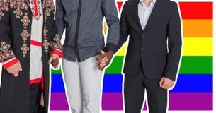 Les hommes de différentes nationalités tiennent des mains dans la perspective du drapeau de LGBT Le concept de la liberté et de l Image stock