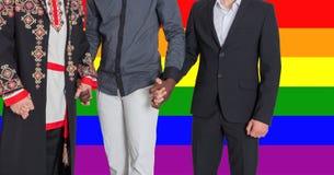 Les hommes de différentes nationalités tiennent des mains dans la perspective du drapeau de LGBT Le concept de la liberté et de l Images libres de droits