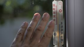 Les hommes de doigts touchent la fenêtre, qui est fixée à un thermomètre à mercure montrant la température en dehors de 32 degrés banque de vidéos