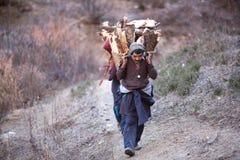 Les hommes de Gorkhas portent le panier lourd en Himalaya Photos stock