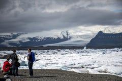 Les hommes de l'Islande se tenant à la neige glaciaire de nature de lagune de Jokulsarlon de lac de glacier aménagent Vatnajokull Images libres de droits