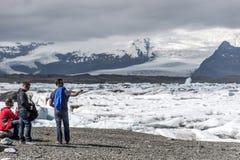 Les hommes de l'Islande se tenant à la neige glaciaire de nature de lagune de Jokulsarlon de lac de glacier aménagent Vatnajokull Image libre de droits