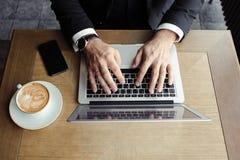 Les hommes de mains se trouvent sur l'ordinateur portable, près d'un téléphone et d'un cappuccino image libre de droits