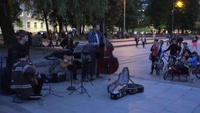 Les hommes de musiciens de rue jouent des touristes et des citoyens de musique 4K banque de vidéos