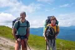 Les hommes de sourire, voyageurs avec des sacs à dos se tiennent sur la montagne Image libre de droits