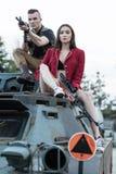 Les hommes de tir s'asseyant sur le réservoir avec des femmes s'approchent de lui Photos libres de droits
