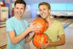 Les hommes effectuent le fléau à partir des billes dans le club de bowling Photos stock