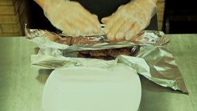 Les hommes enveloppe la viande dans l'aluminium banque de vidéos