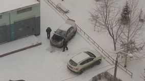 Les hommes essayent de réparer une voiture sur le sort de parc couvert par neige dans la région de dortoir banque de vidéos