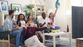 Les hommes et les fans de femmes apprécient le jeu de sports à la TV à la maison riant étreindre banque de vidéos