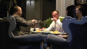 Les hommes et les femmes boivent du café et les cocktails, sur la table sont des sushi, le mouvement lent Tir de glisseur banque de vidéos