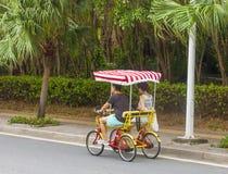 Les hommes et les femmes montent une bicyclette à quatre roues Images libres de droits
