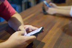 Les hommes et les femmes utilisent le smartphone photos stock