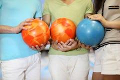 Les hommes et la femme retiennent des billes dans le club de bowling Image libre de droits