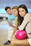 Les hommes et la femme s'asseyent dans le club de bowling Images stock
