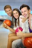 Les hommes et le femme retiennent les billes, pouce vers le haut dans le club de bowling Image stock
