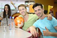 Les hommes et le femme s'asseyent à la table dans le bowling Photos stock