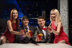 Les hommes et les femmes ont soulevé leurs verres avec des cocktails Photos stock
