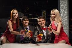 Les hommes et les femmes ont soulevé leurs verres avec des cocktails Images stock