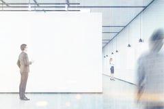 Les hommes et une femme regardent les bannières vides dans une galerie d'art, Photographie stock libre de droits