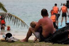 Les hommes européens prennent soin du bébé sur une plage Image libre de droits