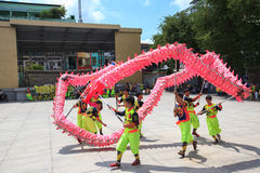 Les hommes exécute la danse de dragon pour pratiquer se préparent à la nouvelle année lunaire à une pagoda Image libre de droits