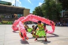 Les hommes exécute la danse de dragon pour pratiquer se préparent à la nouvelle année lunaire à une pagoda Images libres de droits
