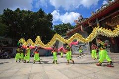 Les hommes exécute la danse de dragon pour pratiquer se préparent à la nouvelle année lunaire à une pagoda Photo libre de droits
