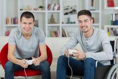 Les hommes jouant des jeux vidéo se concentrent sur la manette photos stock