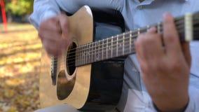 Les hommes joue la guitare acoustique noire dehors en parc jaune d'automne banque de vidéos