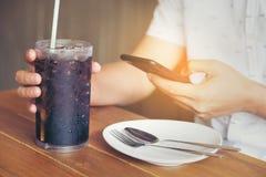 Les hommes jouent la prise de smartphone et de main du clip D mou en verre en café au sujet de photographie stock libre de droits