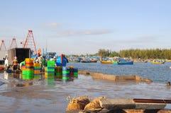 Les hommes locaux nettoient leurs paniers qui ont été employés pour transporter des poissons du bateau au camion Photos libres de droits