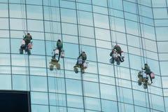 Les hommes nettoient les gratte-ciel en verre images libres de droits