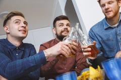 Les hommes observant le sport à la TV grillent ensemble à la maison pour le plan rapproché d'équipe Images libres de droits