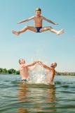 Les hommes ont jeté le garçon dans l'eau Image libre de droits