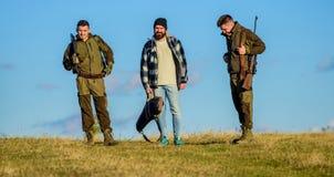 Les hommes portent des fusils de chasse Chasseurs avec le jour ensoleillé d'automne de promenade d'armes à feu Chasse comme passe photos stock