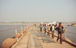 Les hommes portent les sacs lourds des marchandises à travers le pont au-dessus de la rivière large le Gange Image libre de droits