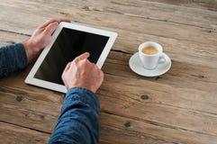 Les hommes presse la tablette d'écran vide pour le bureau en bois Photos libres de droits