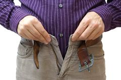 Les hommes remet incapable de fermer le pantalon dû au gainingweight Photographie stock libre de droits