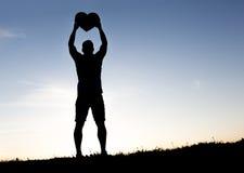 Les hommes remet tenir la silhouette de coeurs sur le coucher du soleil de silhouette Images libres de droits
