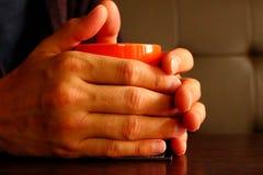 Les hommes remet tenir la tasse orange avec le thé noir ou le café noir sur la table en bois brune en tant que concept confortabl Photo stock