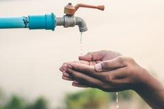 Les hommes remettent attendent pour boire l'eau dans le manque d'eau images libres de droits