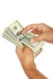Les hommes remettent tenir cent billet d'un dollar sur le fond blanc Images stock