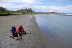 Les hommes s'asseyent à la côte de rivière de plage Photo stock