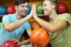 Les hommes s'asseyent près des étagères avec des billes dans le club de bowling Photo stock