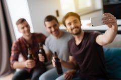 Les hommes s'asseyent sur le divan et la bière potable Un homme fait un selfie avec les amis et la bière Images libres de droits