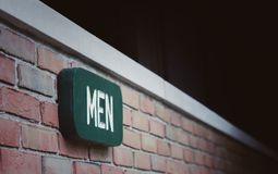 Les hommes se connectent le mur de briques Images stock
