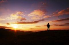 Les hommes silhouettent sur le coucher du soleil Images stock