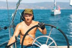 Les hommes skipper sur le yacht pendant les courses de voile en mer Images libres de droits